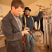 Actors take a break backstage between re-enactments of the infamous gunfight at the OK Corral in Tombstone, Arizona. Tim Fattig (as Frank McLaury) is the actor group leader, pictured here reloading blanks into a gun. Jeremy Caron (as Ike Clanton) is in the background.