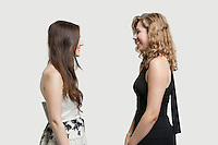 Two female friends looking at each other and smiling over gray background