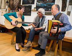 Pictured: Maggie Chapman took some guitar lessons from David Francis while accordianist Stan Reeves provided the melody<br /> <br /> Greens co-convenor Maggie Chapman visited TradFest, a traditional arts festival, which opened in Edinburgh today and learnt more about the importance of culture to our society and our economy, looking at the tourism potential of festivals and how technology can enable this.<br /> <br /> Ger Harley | EEm 27 April 2016