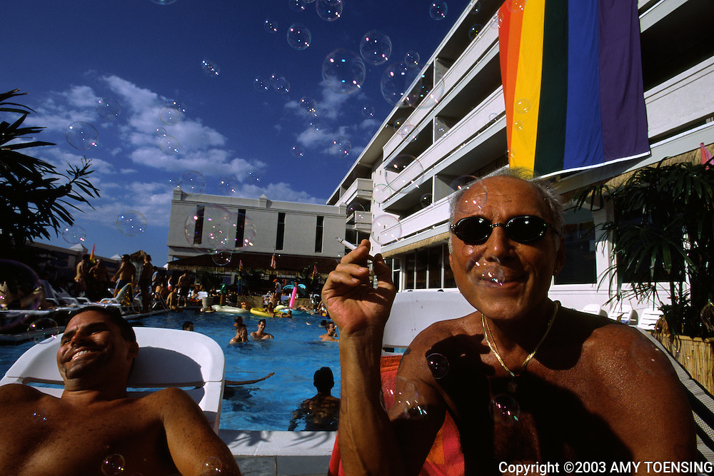 ASBURY PARK, NJ - JULY 19: Vacationers share a laugh at the Paradise Club July 19, 2003 in Asbury Park, New Jersey. Asbury Park is being promoted as a gay destination in order to bring more visitors to the area. The Jersey Shore, a 127 mile stretch of coastline known for its variety of beaches, boardwalks, small towns, natural beauty and summer crowds, has been a popular summer destination for over a century. (Photo By Amy Toensing)