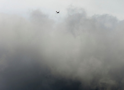 © Licensed to London News Pictures. 03/03/2014. LONDON, UK A british Airways plane flies over storm clouds in West London this afternoon 3rd March 2014. Photo credit : Stephen Simpson/LNP
