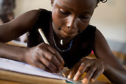 A girl draws in her notebook at the Essaout primary school in the village of Essaout, Senegal, on Thursday June 14, 2007...