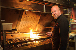 "MALDEGEM, BELGIUM - JUNE-18-2011 - Peter De Clercq, Grill Master, TV host, and the 2003 World BBQ Champion, designed and built his grill from scratch, installing a large metal hopper at the back of the grill, where whole oak, birch, apple, and cherry logs are burned to embers, which fall down a chute under the grill grates. ""Charcoal has the taste burned out of it,"" De Clercq says. ""You can't beat the flavor of wood."" (Photo © Jock Fistick)"