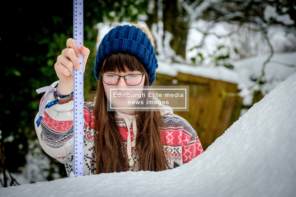 Seonaid Wilson from Biggar, South Lanarkshire measures the depth of snow on a car.  Almost nine inches (22.5cm) of snow has fallen in the past 24 hours with more forecast.<br /> <br /> (c) Andrew Wilson   Edinburgh Elite media