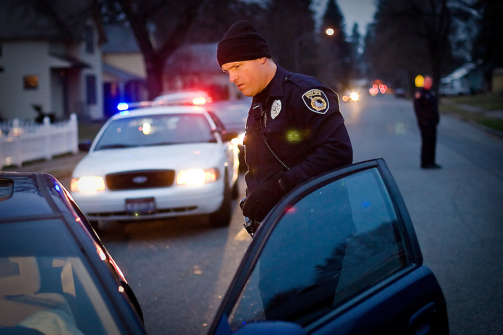 JEROME A. POLLOS/Press..Coeur d'Alene Police officer Hank Dunham looks for evidence of drunk driving after a suspect was arrested Friday.