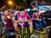 27 FEBRUARY 2019 - BANGKOK, THAILAND: Porters in Pak Klong Talat, the Bangkok flower market, check their smart phones while they wait for customers. Bangkok, a city of about 14 million, is famous for its raucous nightlife. But Bangkok's real nightlife is seen in its markets and street stalls, many of which are open through the night.       PHOTO BY JACK KURTZ