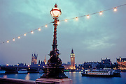 A street lamp with Big Ben, the Thames River,  and WestminsterCathedral in the background at night. London, England.