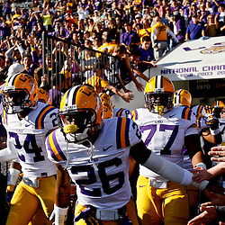 November 17, 2012; Baton Rouge, LA, USA  LSU Tigers players safety Ronald Martin (26), cornerback Tharold Simon (24) and defensive tackle Josh Downs (77) take to the field before a game against the Ole Miss Rebels at Tiger Stadium. LSU defeated Ole Miss 41-35. Mandatory Credit: Derick E. Hingle-US PRESSWIRE