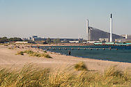 A view of Amager Strandpark – a beach on the island of Amager just south of the capital, Copenhagen. In the background stands the Bjarke Ingels Copenhill Ski Slope