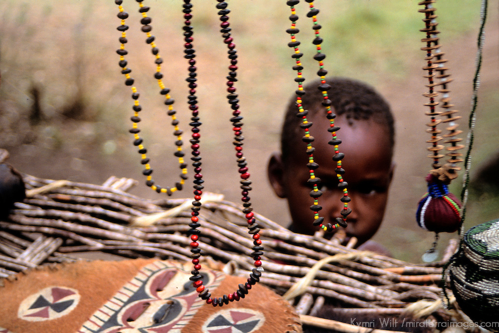 Africa, Kenya, Maasai Mara. A young Masai boy peeks from under the makeshift display of handmade jewelry and handicrafts at Olanana in the Maasai Mara.