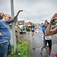 Nederland, Amsterdam , 22 september 2013.<br /> Dam tot Dam loop 2013.<br /> Deelnemers lopen over de Stoombootweg in Amsterdam Noord, aangemoedigd door bewoners.<br /> Op de foto een buurtbewoner zorgt voor verkoeling van de vele deelnemers.<br /> Foto:Jean-Pierre Jans