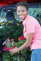 Woman Loading Her Potted Plants into Trunk of Car