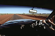 Driving the Stuart Highway north of Alice Springs. Australia. View through windshield with driver on right side.