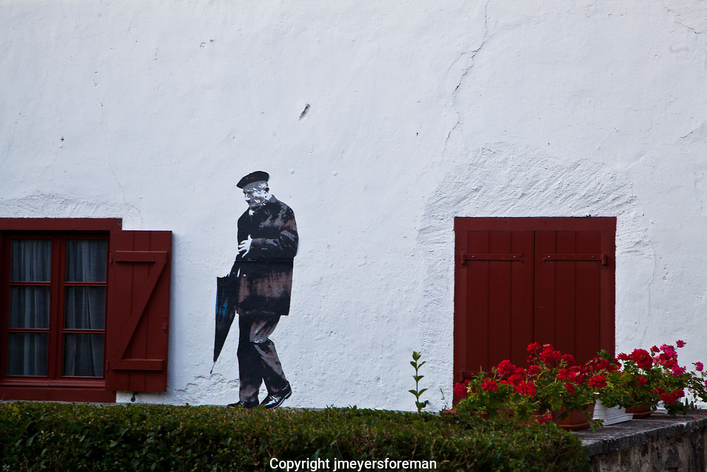 Wall Mural in the village of Burguete (Auritz) Spain of a gentleman going for a walk with his umbrella