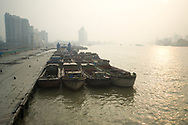 Early morning view of cargo ships docked on the Hongkou side of the Huangpu River in Shanghai, China, one of the worlds busiest ports.  Air pollution, particularly from SO2 is a major problem in Shanghai.  Most of the pollution comes from coal-burning smoke and vehicle emissions.