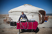 """A man sets up DJ booth in front of traditional portalble wood-framed house """"yurt."""""""