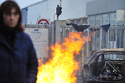 A woman stands in front of flame during a protest at the entrance of the Ford Genk assembly factory, in Genk of Belgium, Jan. 9, 2013, the first day to resume the production in 2013. A thin majority of workers voted to re-start to work for 40 more days in 2013 in an agreement between the direction and unions earlier in the week, but some others decided to block all access to the plant in protest. Ford Europe announced on October 24, 2012 to close its Genk plant at the end of 2014, threatening 4,300 jobs as slumping demand across Europe leaves companies with too much capacity, Brussels, Belgium, January 9, 2013. Photo by Imago / i-Images...UK ONLY