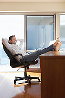 Man sitting in office with feet up on desk.