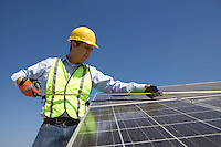 Maintenance worker measures solar cells in Los Angeles California