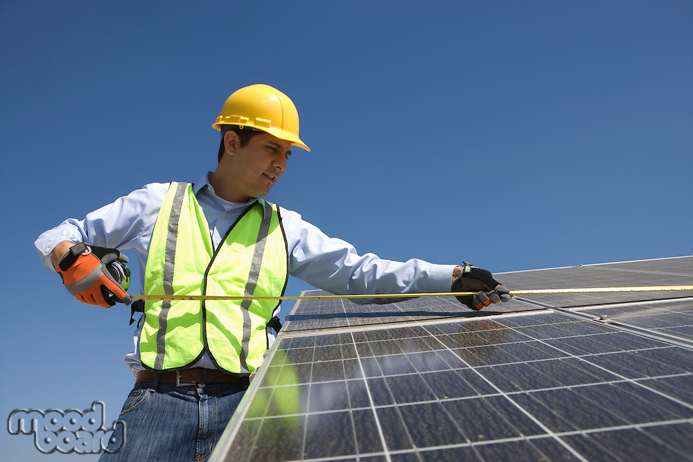 Maintenance worker measures solar cells in Los Angeles California