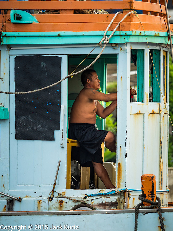 01 OCTOBER 2015 - MAHACHAI, SAMUT SAKHON, THAILAND:  A man steers aThai fishing trawler up the Tha Chin River in Mahachai, one of Thailand's largest fishing ports. Thailand's fishing industry had been facing an October deadline from the European Union to address issues related to overfishing and labor practices. Failure to adequately address the issues could have resulted in a ban on Thai exports to the EU. In September Thai officials announced that they had secured an extension of the deadline. Officials did not say how much extra time they had to meet the EU goals. Thailand's overall annual exports to the EU are between 23.2 billion Thai Baht and 30 billion Thai Baht (US$645 million to US $841 million). Thailand's total fish exports were worth about 110 billion baht in 2014.   PHOTO BY JACK KURTZ