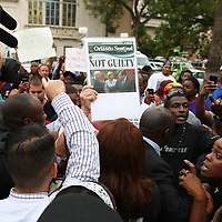 "A George Zimmerman supporter holds up a sign saying not guilty, during  the No Justice No Peace- ""March Against Gun Violence""  walk from Lake Eola in downtown Orlando, to the Orange County Courthouse on Wednesday, July 17, 2013. The march was organized by the Modarres Law Firm and Orlando attorney Natalie Jackson, one of the attorneys for Trayvon Martins parents. (AP Photo/Alex Menendez)"