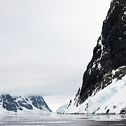 "Steep rocky cliffs rise out of the water along the narrow Lemaire Channel on the western side of the Antarctic Peninsula. The Lemaire Channel is sometimes referred to as ""Kodak Gap"" in a nod to its famously scenic views."
