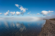 View along lakeshore with fog clearing to reveal blue water under blue sky, Yellowstone Lake, WY, © 2005 David A. Ponton