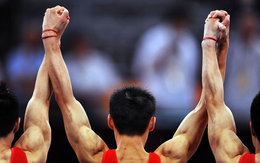 MEN'S TEAM GYMNASTICS  - 081208 - Chinese gymnasts hold their hands aloft in unity as they are announced as winners of the gold medal in the men's team competition at the Olympic Games in Beijing, China.