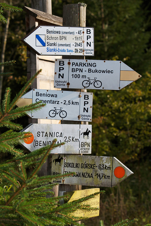 Signpost marking hiking and biking trails at the entrance of Bieszczady National Park. Bukowiec, Poland.