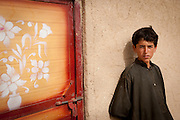 An Afghan boy watches a patrol pass in Marjah.