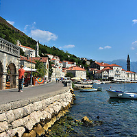 Woman Strolling Waterfront in Perast, Montenegro<br /> While strolling along Persat's shoreline you will find numerous palaces previously owned by captains of the Venetian navy, shipbuilders and former elite families. During its history, this town had the prestigious Nautica naval college, was the home to four successful shipyards and harbored over 100 ships. You would hardly guess its illustrious past by seeing the modest boats tethered in the bay.