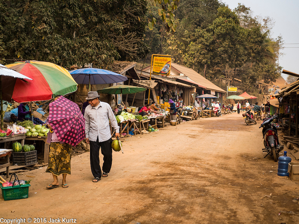 11 MARCH 2016 - LUANG PRABANG, LAOS:   People walk through the market on the main road in the community of Chomphet, across the Mekong River from Luang Prabang. Laos is one of the poorest countries in Southeast Asia. Tourism and hydroelectric dams along the rivers that run through the country are driving the legal economy.     PHOTO BY JACK KURTZ