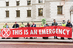 "© Licensed to London News Pictures. 03/10/2019. London, UK. Extinction Rebellion protesters stage a protest after using a fire engine to spray the front of the Treasury building with fake blood. Extinction Rebellion said it wanted to highlight the ""inconsistency between the UK Government's insistence that the UK is a world leader in tackling climate breakdown, while pouring vast sums of money into fossil exploration and carbon-intensive projects"". Photo credit: Ray Tang/LNP"