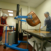 Sister Kate Mehlmann spreads the caramel candy mixture on a cooling table as Sister Julie Doorak mans the hydraulics that pours the candy from a large copper kettle.  The Cistercian Order of Our Lady of the Mississippi Abbey near Dubuque, Iowa,  use their expanding candy production to financially support their order and a developing missionary monastery in Tautra, Norway.  The community of 22 Roman Catholic nuns follow Jesus Christ through a life of prayer, silence, simplicity and ordinary work.  Their home is a beautiful monastery which sits high on a bluff, overlooking the Mississippi River