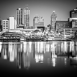 Picture of Peoria Illinois skyline at night in black and white with downtown city buildings reflection on the Illinois River and the Spirit of Peoria paddlesheel riverboat.