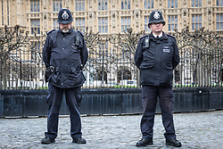 © Licensed to London News Pictures. 29/03/2017. London, UK. Two policemen stationed at Carriage Gate observe a minute's silence held at 14:40, exactly one week after Khalid Masood began a terrorist attack on Westminster on 22 March 2017. PC Keith Palmer was killed by the attacked after he entered Carriage Gate. Photo credit: Rob Pinney/LNP