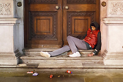 © licensed to London News Pictures. London, UK 01/01/2014. A man falls asleep outside a government office on Whitehall, London whilst celebrating the New Year at the first hours of 2014. Photo credit: Tolga Akmen/LNP