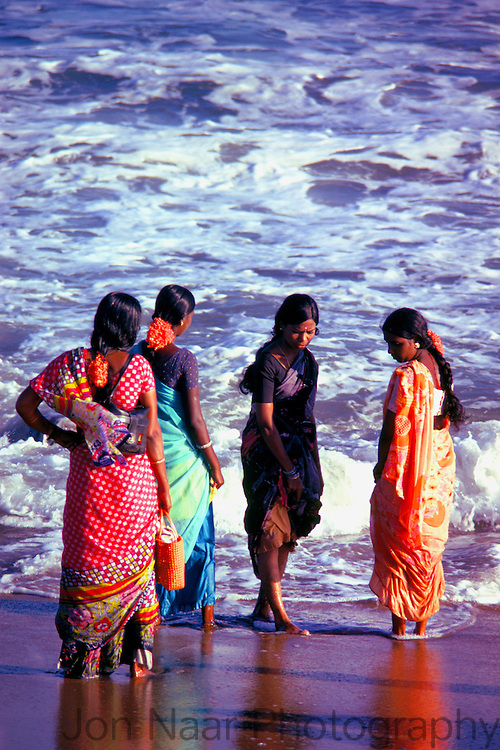 Five women in saris walking at the seashore. Taken in 1979 with a 35 mm Nikon FM.