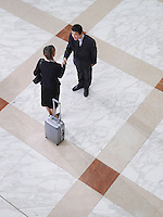 Businessman and businesswoman shaking hands elevated view