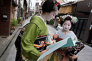 Miehina (in green kimono), a 20 year old maiko ( an apprentice geisha) from the Miyagawacho district of Kyoto talks with a fellow maiko girl in the street, Japan, Sunday, May 18th 2008.