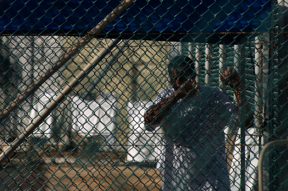 "A detainee clutches a fence at Camp 4 at the detention facility in Guantanamo Bay, Cuba. Camp 4 is a communal style camp where more compliant detainees live in small groups and have access to a more open air environment. Approximately 250 ""unlawful enemy combatants"" captured since the September 11, attacks on the United States continue to be held at the detention facility.(Image reviewed by military official prior to transmission)"