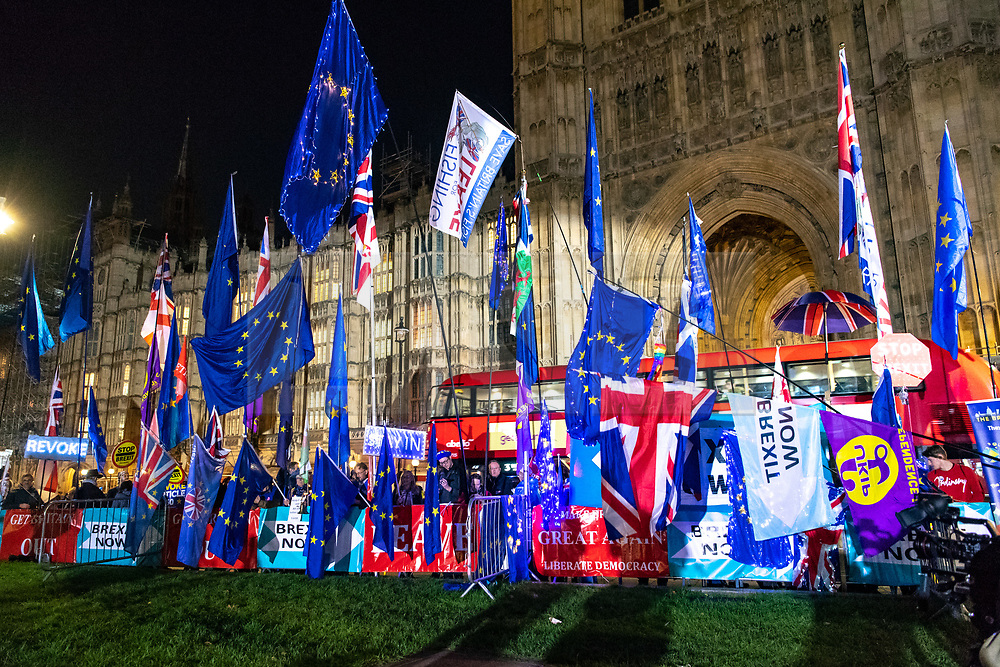 """© Licensed to London News Pictures. 22/10/2019. London, UK. People gather outside The Palace of Westminster in front of College Green ahead of crucial votes for PM Boris Johnson government. MPs backed his Withdrawal Agreement Bill - but minutes later voted against the timetable, placing Brexit """"in limbo"""". Photo credit: Guilhem Baker/LNP"""