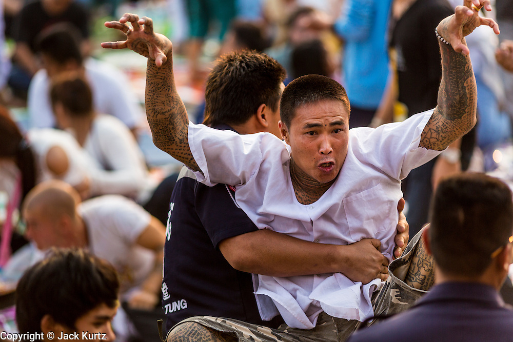 "15 MARCH 2014 - NAKHON CHAI SI, NAKHON PATHOM, THAILAND: A man in a trance rushes the stage at the Wat Bang Phra tattoo festival. Wat Bang Phra is the best known ""Sak Yant"" tattoo temple in Thailand. It's located in Nakhon Pathom province, about 40 miles from Bangkok. The tattoos are given with hollow stainless steel needles and are thought to possess magical powers of protection. The tattoos, which are given by Buddhist monks, are popular with soldiers, policeman and gangsters, people who generally live in harm's way. The tattoo must be activated to remain powerful and the annual Wai Khru Ceremony (tattoo festival) at the temple draws thousands of devotees who come to the temple to activate or renew the tattoos. People go into trance like states and then assume the personality of their tattoo, so people with tiger tattoos assume the personality of a tiger, people with monkey tattoos take on the personality of a monkey and so on. In recent years the tattoo festival has become popular with tourists who make the trip to Nakorn Pathom province to see a side of ""exotic"" Thailand.   PHOTO BY JACK KURTZ"