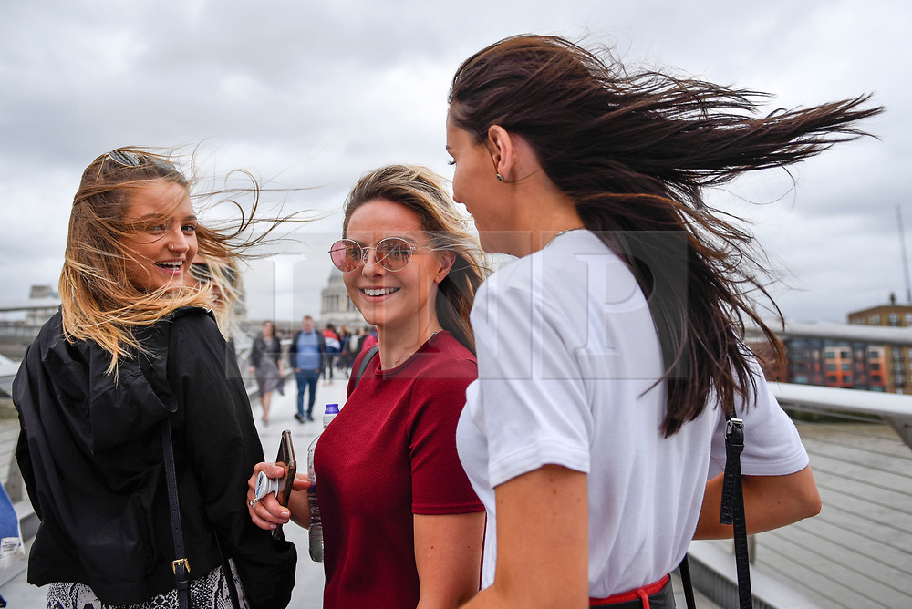© Licensed to London News Pictures. 10/08/2019. LONDON, UK.  Tourists cross the Millennium Bridge during windy conditions.  Much of the UK forecast to be subject to strong winds for the weekend.  Photo credit: Stephen Chung/LNP