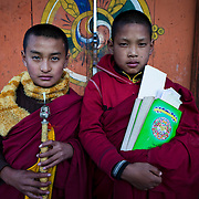 Novice monks with flutes (Rgya-Gling) outside the temple of Wangdichholing Palace built in 1857 as the Kingdom's first palace, Bumthang, Bhutan, Asia