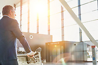 Mature businessman pushing luggage cart for check in at airport