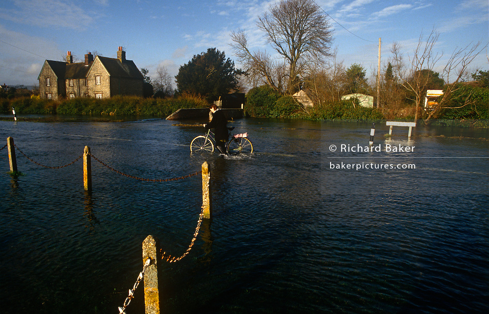 A cyclist struggles through flood water in the West Sussex village of Lavant. In ankle-deep water, the rider makes her way slowly along the country lane in the village, trying not to fall over or down a hidden open manhole. Lavant is a village just north of the city of Chichester. It is made up of two parts, Mid Lavant and East Lavant, and takes its name from the River Lavant which flows from East Dean. This area has been prone to flooding for several years and houses around the rising rivers can be blighted with insurance companies refusing future cover.