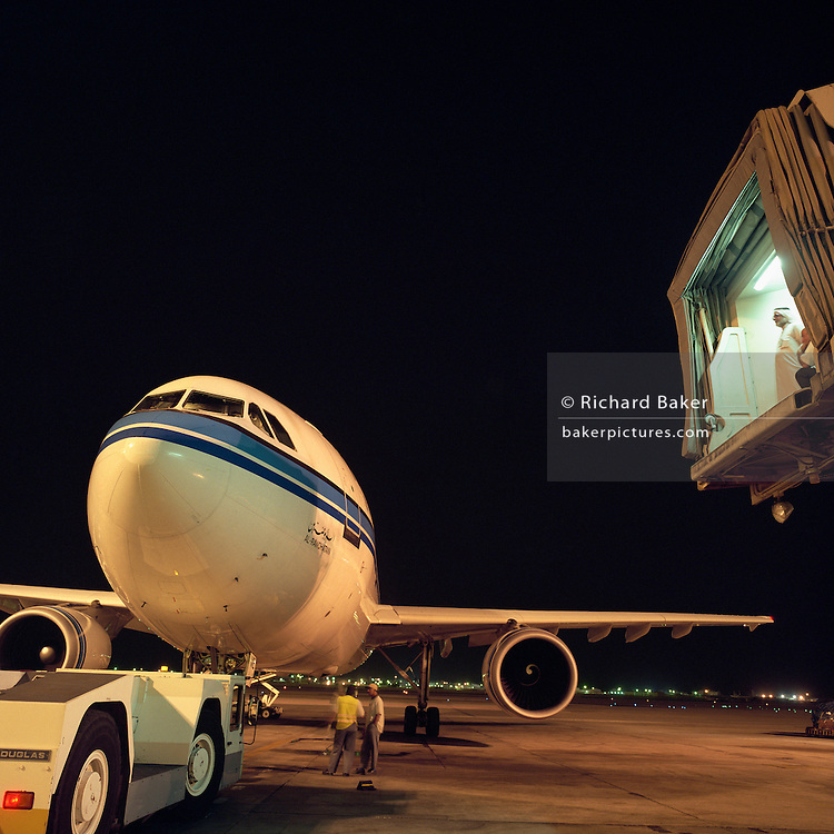 On a hot night at Bahrain International Airport, a Boeing airliner is about to be pushed backwards and start its engines. Two airport agents wearing traditional Arab dress stand patiently high up on the air bridge (that joins the aircraft fuselage during its turnaround time), several metres above ground level, ensuring no last-minute problems occur before departure. This Gulf State is, a key hub airport in the region, providing a gateway to the Northern Gulf. The airport is the major hub for Gulf Air which provides 52% of overall movements. It is also the half-way point between Western Europe and Asian destinations such as Hong Kong and Beijing. Picture from the 'Plane Pictures' project, a celebration of aviation aesthetics and flying culture, 100 years after the Wright brothers first 12 seconds/120 feet powered flight at Kitty Hawk,1903. .