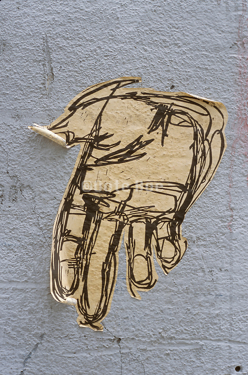 ripped paper drawing of a hand adhered to a wall